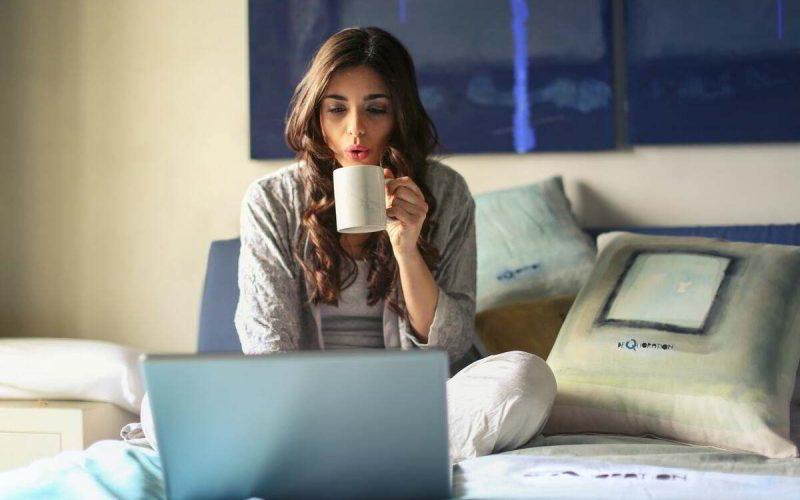 donna beve caffe davanti al pc