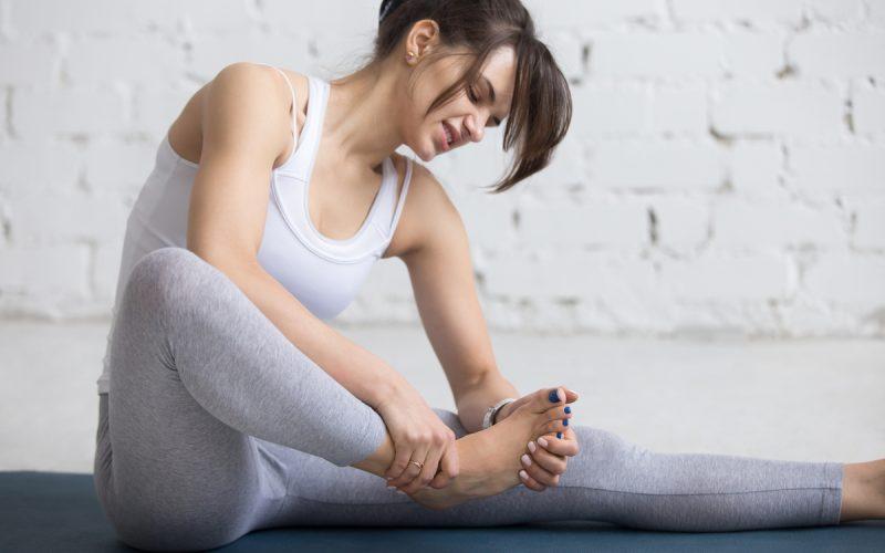 Donna con un crampo al piede