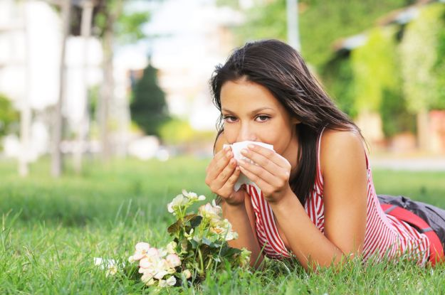young woman in green park, spring allergy and pollen of flower