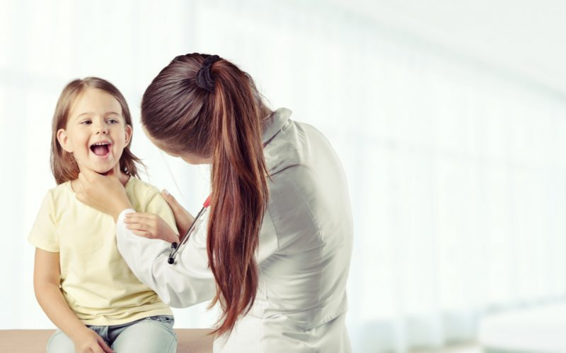 Medico visita una bambina con gli orecchioni