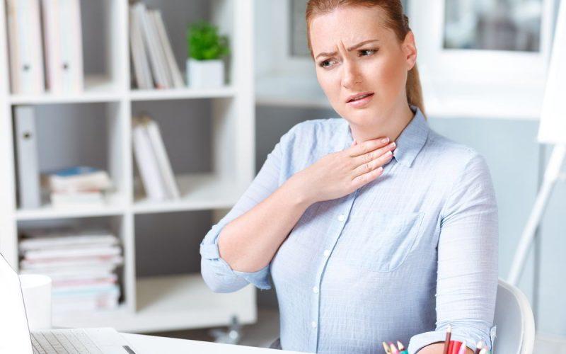 donna sofferente si tocca la gola