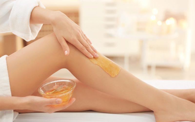 Donna che si spalma la ceretta sulla gamba