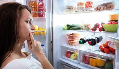 Ragazza indecisa davanti al frigorifero