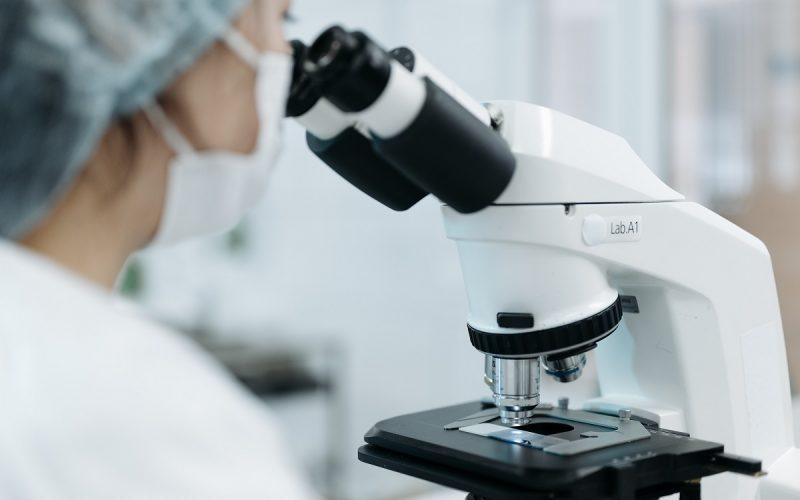 studioso che osserva al microscopio